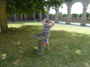 Cheeky grandson Leon in the ruined cloisters at Le Tronchet